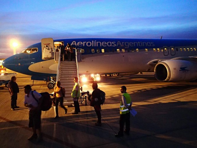 An Aerolineas Argentinas plane with guests disembarking on a staircase.