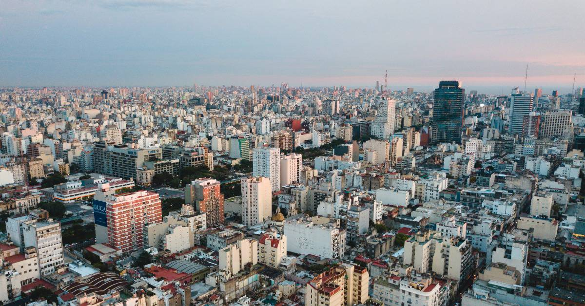 An aerial view of the sprawling Buenos Aires cityscape in front of a blue and pink sky.