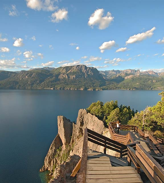 A visitor on a pathway overlooking a scenic lake surrounded by mountains near Bariloche.