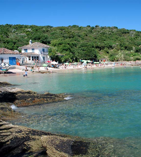 Visitors on a beach in Buzios with crystal blue water and surrounded by lush vegetation.