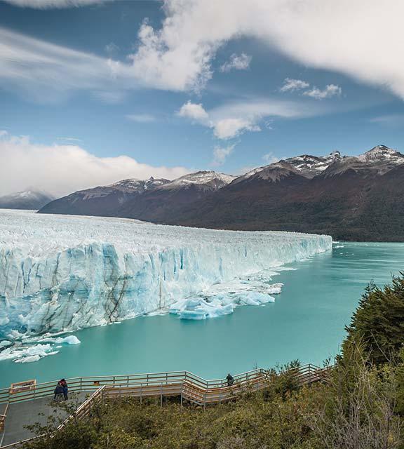 Visitors on a walkway admiring the enormous, blue-colored Perito Moreno glacier.