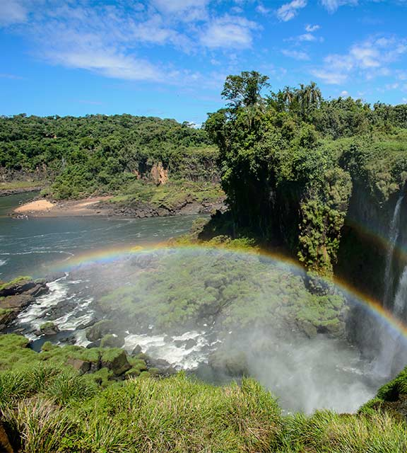 A full rainbow arch next to a waterfall at Iguazu Falls with lush greenery surrounding on all sides.