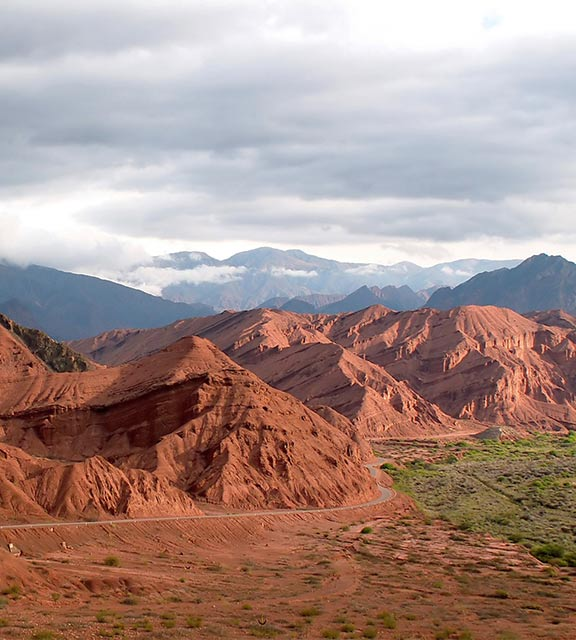 A road hugs the side of mountains made of red rock near the northern Argentinian city of Salta.