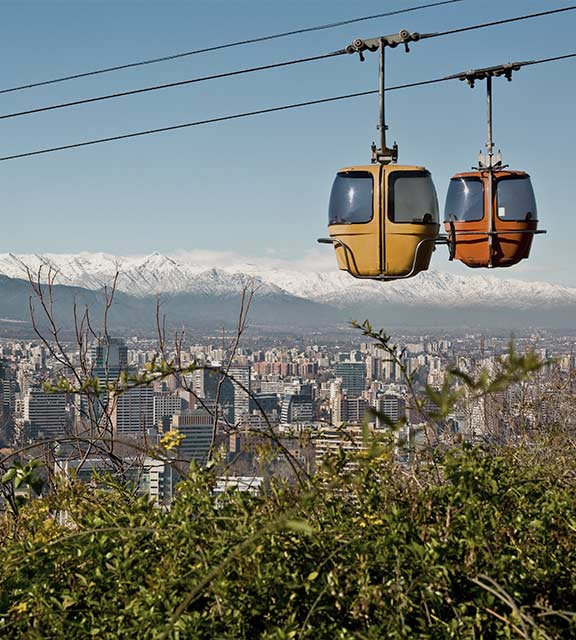 A pair of cable cars overlooking the city of Santiago with the Andes Mountains as a backdrop.