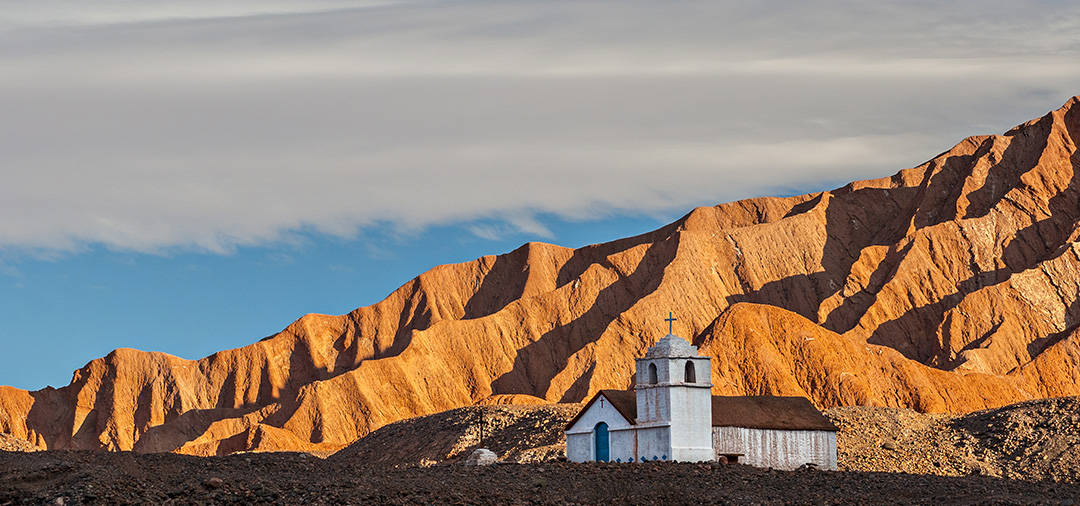 A historic church overlooked by imposing golden-colored mountains in the Atacama Desert.