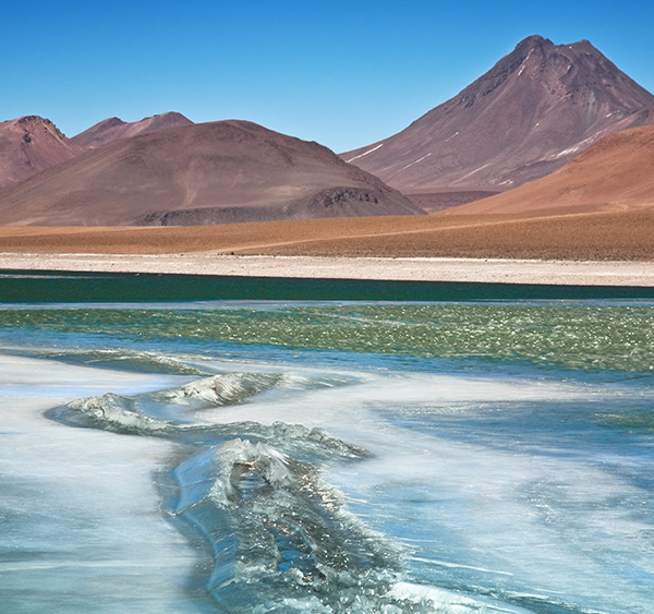 The shimmering water of a lagoon overlooked by red and orange mountains in Chile's Atacama Desert.