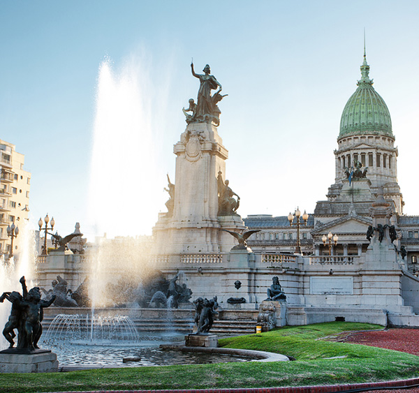 A water fountain and statues in front of the Palace of the Argentine National Congress.