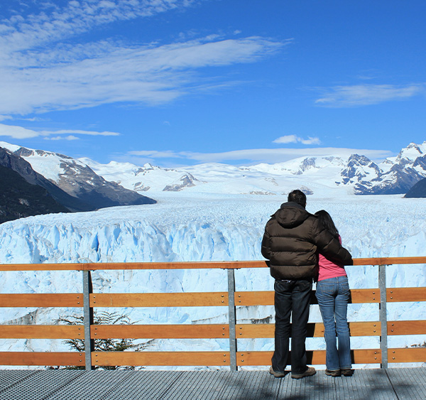 A couple on a walkway looking out at the enormous Perito Moreno glacier in Argentine Patagonia.
