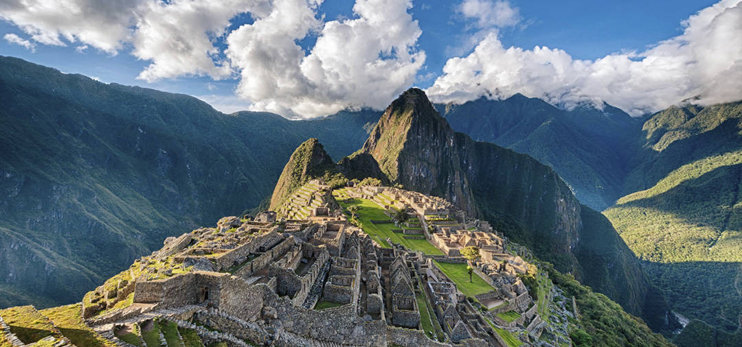 The Inca ruins of Machu Picchu with the Andes Mountains as a backdrop on a partly cloudy day.