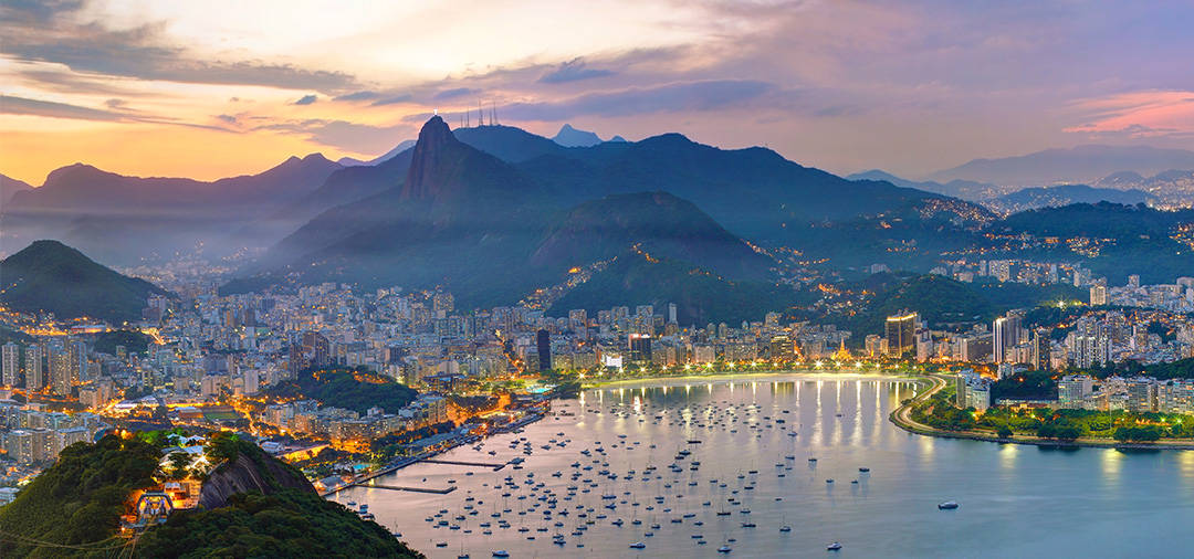 A panoramic view of Rio de Janeiro and the surrounding mountains, lit up in the evening.