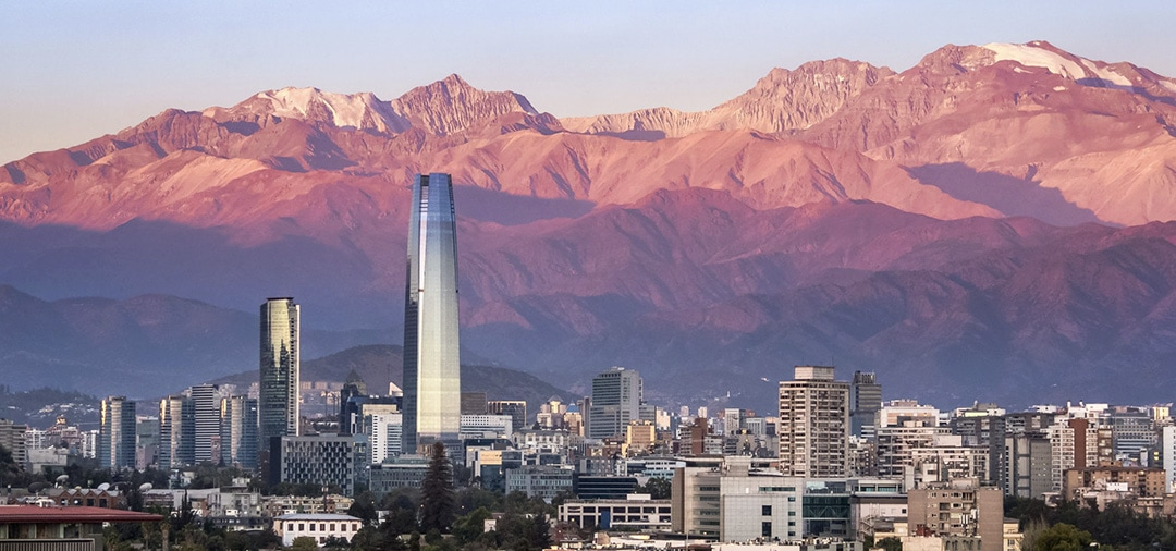 The modern buildings of Santiago overlooked by the Andes Mountains as the sun sets.