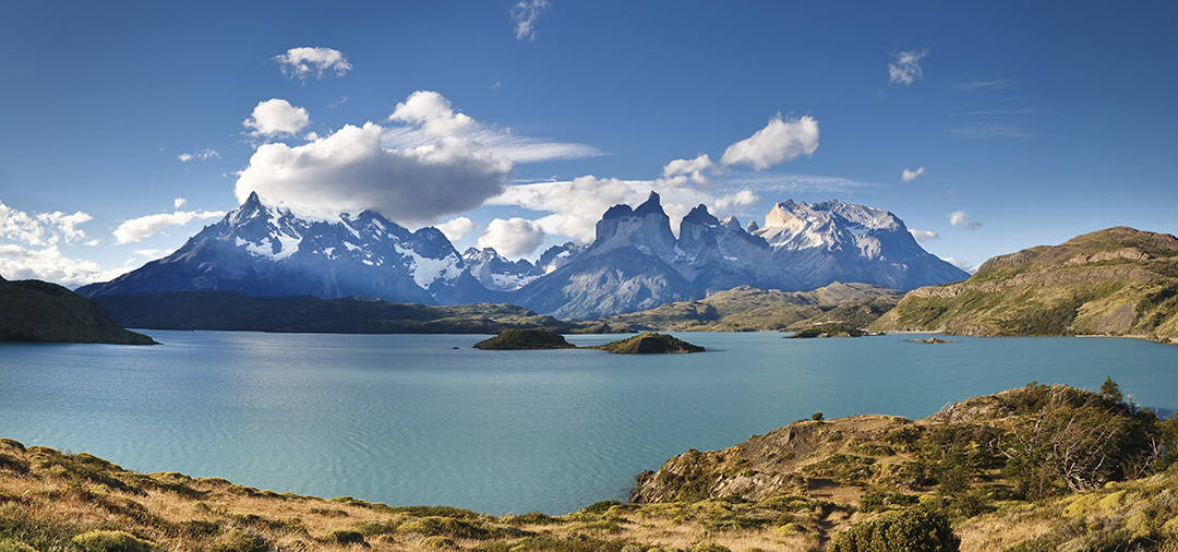 A blue lake overlooked by snow-capped peaks as well as the back of the iconic Torres del Paine.