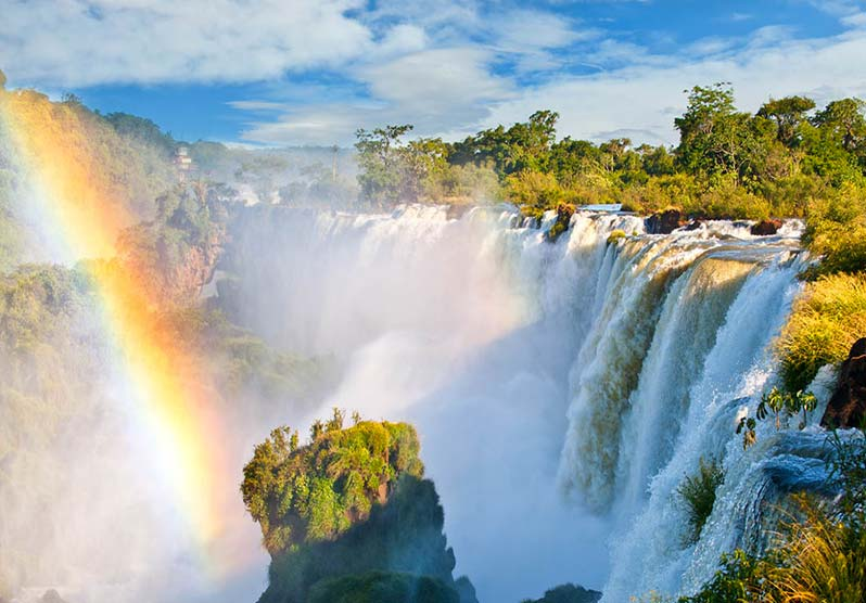 A rainbow forming in the mist over Iguazu Falls, the largest waterfall on earth.