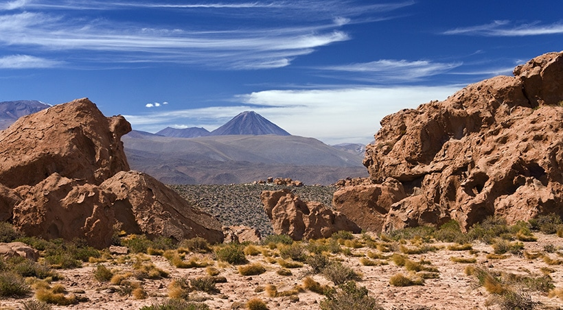 Rock formations and desert landscape with a volcano visible in the distance in the Atacama Desert.