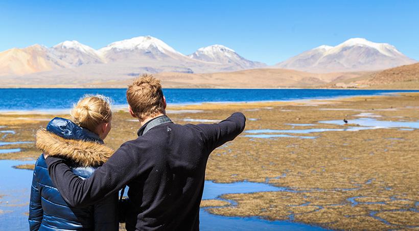 A couple visiting Laguna Chaxa, one of the many scenic lagoons near Chile's San Pedro de Atacama.