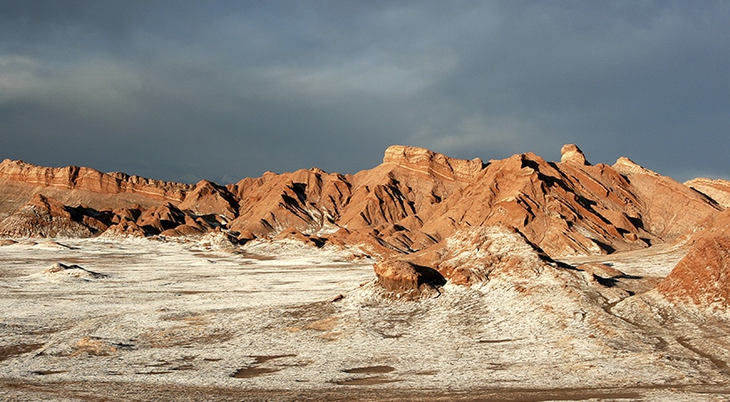 The Atacama Salt Flats surrounded by rugged terrain and interesting rock formations.