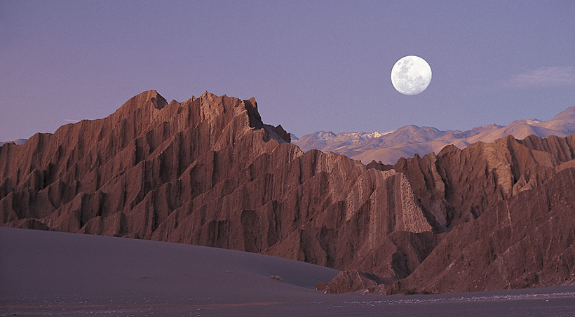 The moon shining down on the impressive rock formations of the Valle de la Luna (Moon Valley).