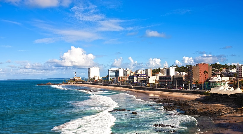 A beach next to the city of Salvador de Bahia, with the Barra lighthouse visible in the distance.