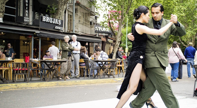 Tourists watching as a well-dressed couple dances the tango in the streets of Buenos Aires.