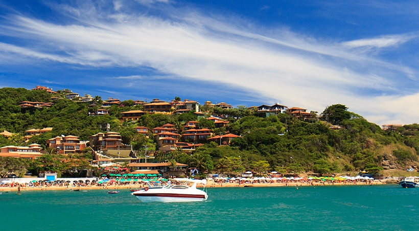 A catamaran in the water off the shore of Búzios, with a beach and many houses in the hills visible.