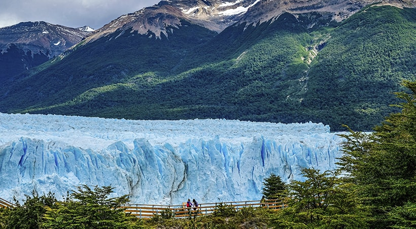 Visitors on a pathway look at a massive blue glacier, with forest-covered mountains behind.