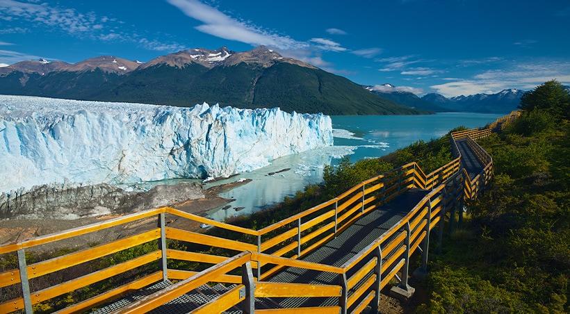 A pathway leading past the blue-tinted Perito Moreno glacier in Los Glaciares National Park.