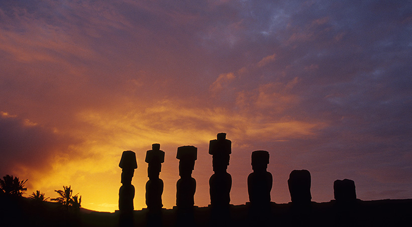 The sun setting over a series of moais, the mysterious stone figures found throughout Easter Island.