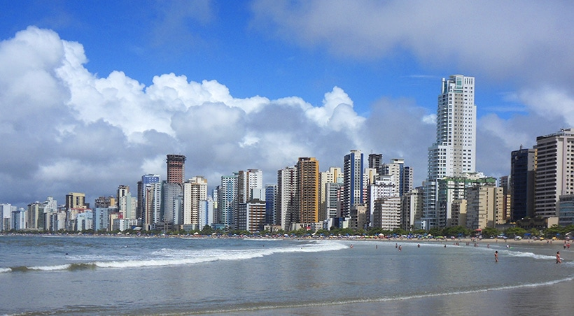 The skyline of Florianópolis overlooking the city's beaches with some beachgoers enjoying the water.