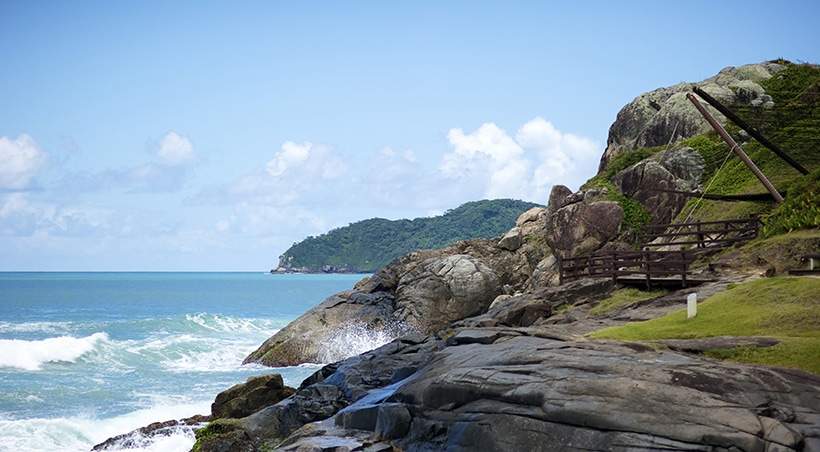 Waves splashing up on some rocks at a park in the Brazilian city of Florianópolis.