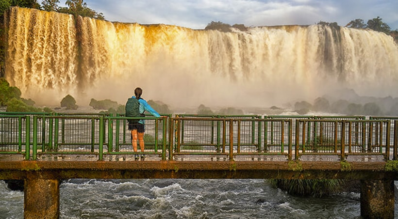 A visitor standing on a small bridge and admiring the awe-inspiring beauty of Iguazu Falls.