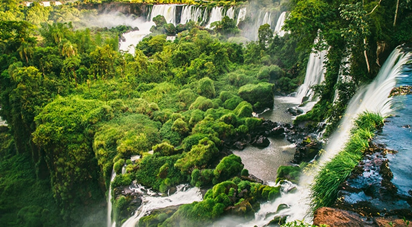 Lush vegetation and a stepped waterfall with more waterfalls in the background at Iguazu Falls.