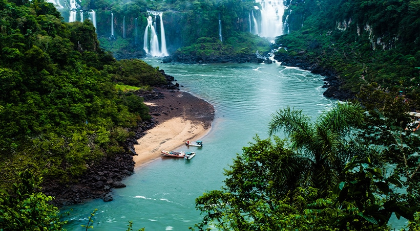 Small boats docked at a beach surrounded by the lush jungle vegetation of Iguazu Falls.