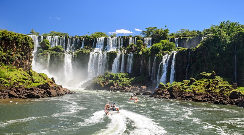 A couple of small boats navigating the water at the foot of the famous Iguazu Falls.