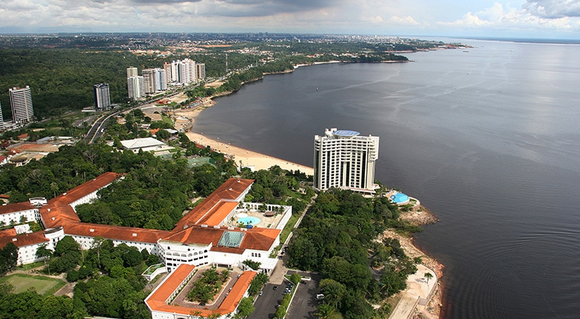 Hotels lining the waterfront, surrounded by tropical forest in the Amazonian city of Manaus.