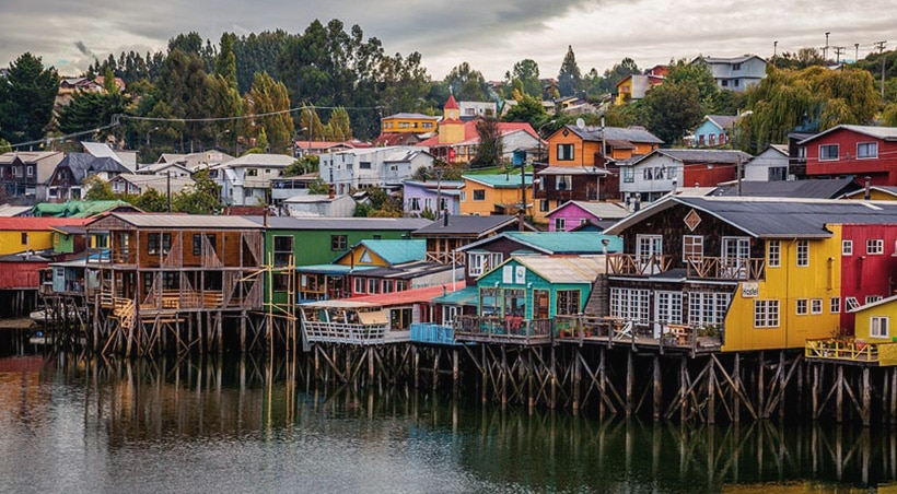 Colorful traditional stilt houses in the water on Chiloé Island in Chilean Patagonia.