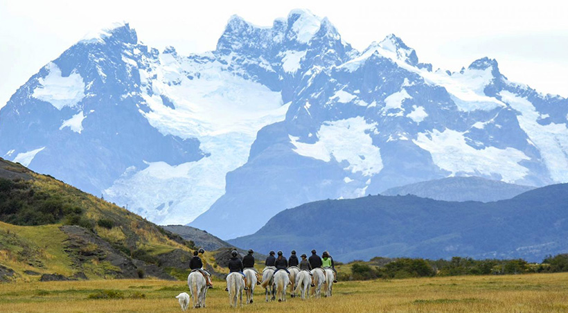 A group of visitors on horseback riding through a valley with imposing mountains towering overhead.