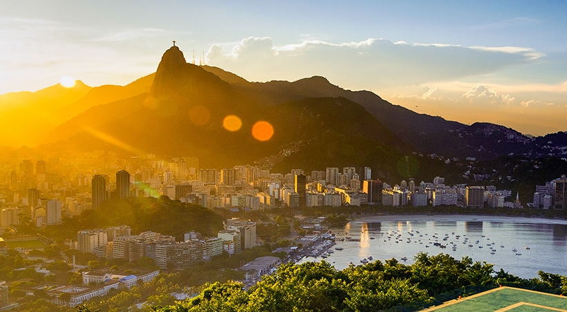 Sunrise over Rio de Janeiro, with the famous Christ the Redeemer statue visible in the distance.