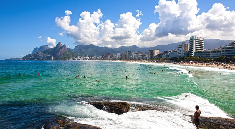 Swimmers and surfers enjoying the water on a sunny day at the beach in Rio de Janeiro.