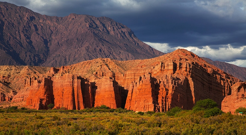 Stunning red rock formations overlooked by a mountain with an ominous dark sky above.