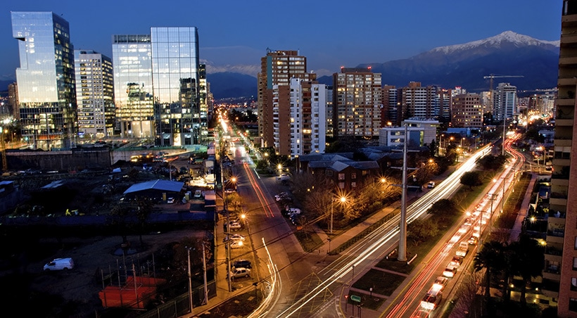 An intersection in Santiago with modern buildings and a snow-capped Andean peak visible.