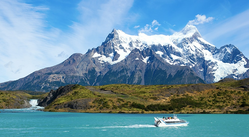 A catamaran navigating the water with mountains overhead in Torres del Paine National Park.