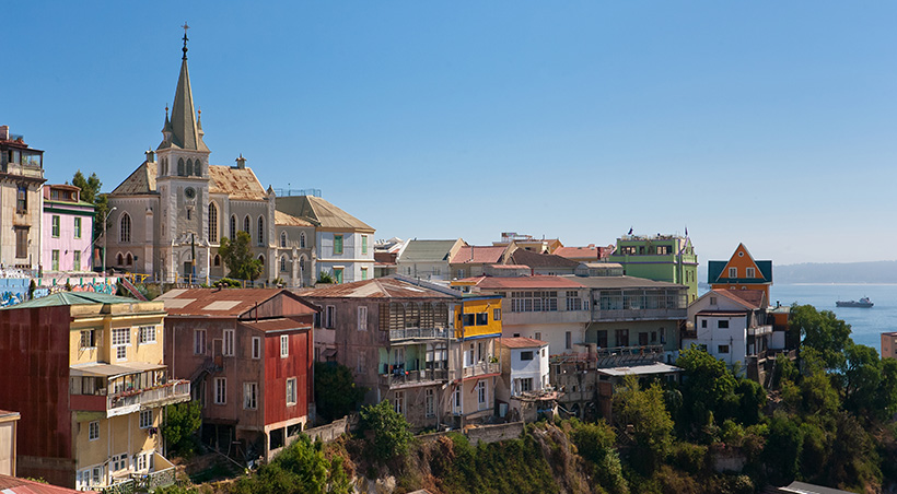 Colorful buildings and a church overlooking the Pacific Ocean in the coastal city of Valparaíso.