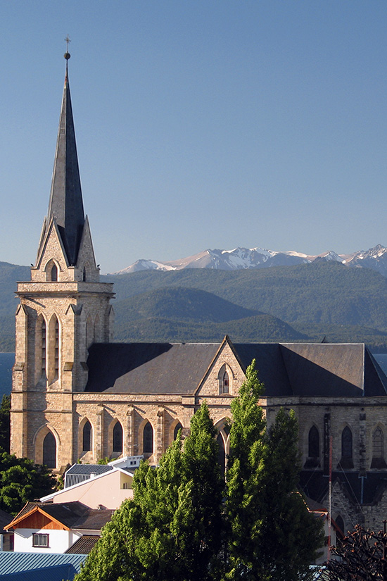 A scenic church overlooked by the snow-capped Andes Mountains in the town of Bariloche, Argentina.