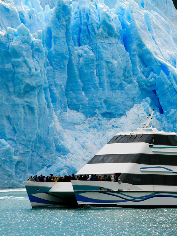A cruise boat full of tourists admiring a massive blue glacier in Los Glaciares National Park.