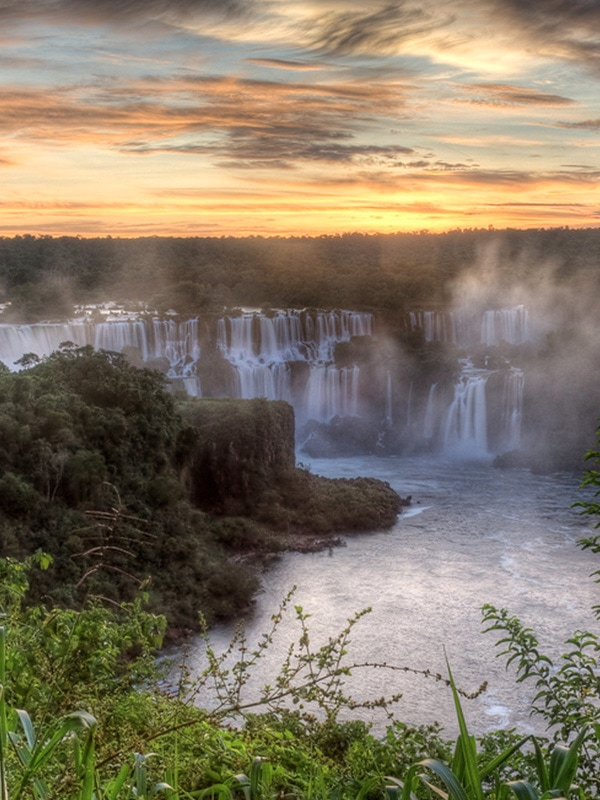 The sun setting over Iguazu Falls, one of the world's largest and most beautiful waterfalls.
