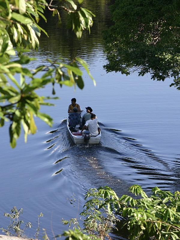 A man piloting a small motorized boat through a waterway in the Brazilian Amazon