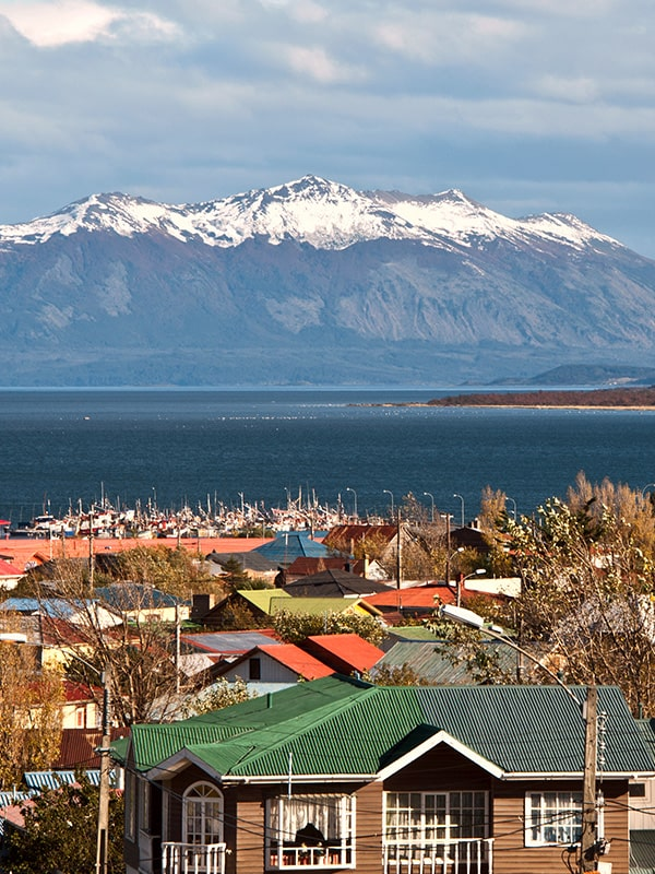 Rooftops of colorful traditional houses with snow-capped mountains overhead in Puerto Natales.