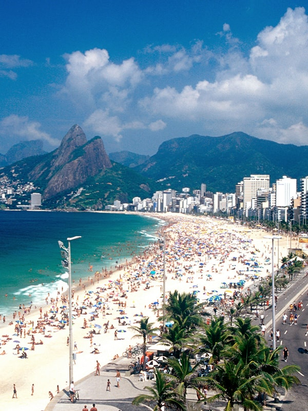 A sunny day with lots of people at one of Rio de Janeiro's world-famous beaches.