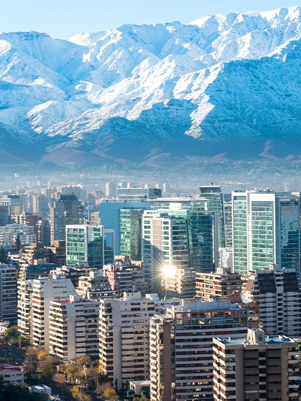 The modern skyscrapers of Santiago with the snow-capped Andes Mountains overhead.