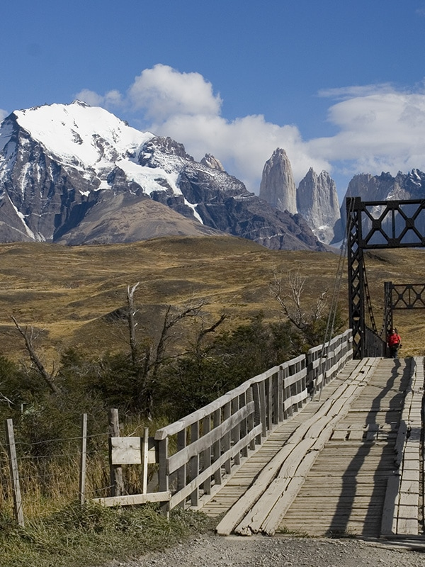 A visitor crossing a bridge in Torres del Paine National Park, with a couple of the peaks visible
